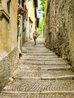 Person walking up a narrrow lane with cobbled steps on the route of the Greenway del Lago di Como, which runs around part of Lake Como. Фото CeriBreeze-Depo
