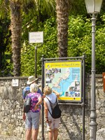 People looking at a map of the Greenway del lago di Como in Lenno on Lake Como. Фото CeriBreeze - Depositphotos