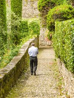 Person walking down a narrrow cobbled path on the route of the Greenway del Lago di Como. Фото CeriBreeze - Depositphotos