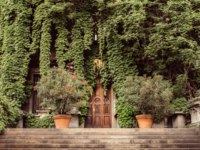 Италия. Архитектура Милана. Rustic wooden door entrance to an Italian villa in Milan covered in beautiful green leaves in the Springtime. Фото Brasilnut-Deposit