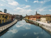 Италия. Милан. Cityscape of Gaggiano, just outside of Milan. Colourful houses reflected in the Naviglio Grande canal waterway. Фото Brasilnut - Depositphotos