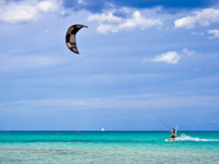Италия. Сардиния. A kitesurfer gliding near the beach La Cinta, Sardinia. Фото sailorr - Depositphotos