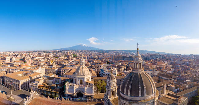 Италия. Сицилия. Катания. Beautiful aerial view of the Catania city near the main Cathedral and Etna volcano on the background. Фото ingus.kruklitis-Depositphotos