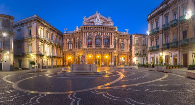 Piazza Vincenzo Bellini and opera house grandiose theater Massimo Bellini in Sicilian Baroque style in the night lighting, Catania, Sicily, Italy. Фото olgacov-Deposit