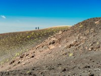 Италия. Сицилия. Катания. Two tourists do a hiking tour around the edge of a volcanic crater, Mount Etna, Sicily, Italy. Фото RS.photography - Depositphotos