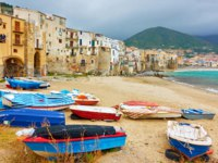 Италия. Сицилия. Панорама Чефалу. Boats and old colorful houses by the sea in the old town of Cefalu in Sicily, Italy. Фото Zoooom - Depositphotos