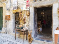 Италия. Сицилия. Чефалу. Wooden sculpture shop and workshop in the old town of the historic village of Cefalu in Sicily, Italy. Фото J2R - Depositphotos