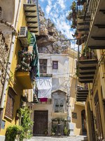 Италия. Сицилия. Чефалу. Narrow street with balconies with hanging clothes in the old town of the historic village of Cefalu in Sicily, Italy. Фото J2R - Depositphotos