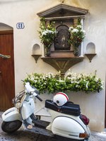 White Vespa motorcycle parked next to a small religious altar adorned in the old town of the historic village of Cefalu in Sicily, Italy. Фото J2R - Depositphotos