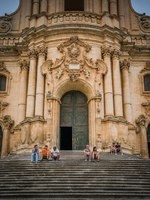 Италия. Сицилия. Модика. Tourists resting on the stairs of the Duomo of San Giorgio in Modica, fine example of sicilian baroque art. Sicily, Italy. Фото e55evu-Deposit
