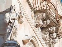 Италия. Сицилия. Рагуза. The baroque statue of St. Francis of Paola sculpted at the corner of Cosentini palace in Ragusa Ibla with mascarons. Фото siculodoc-Deposit