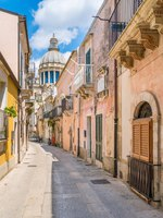 Италия. Сицилия. Рагуза. A narrow and picturesque road in Ragusa Ibla with the dome of Saint George Duomo. Sicily, southern Italy. Фото e55evu - Depositphotos