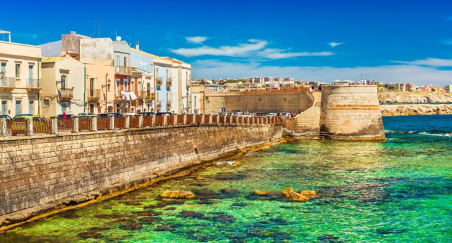View of an embankment in Ortigia. Picturesque view of the historical part of Syracuse. Beautiful coastline, transparent water of The Ionian Sea. Фото RS.photography-Dep