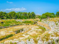Greek Theatre of Syracuse Sicily. Ruins of the Roman Amphitheater in Syracuse, Sicily, Italy. Фото Dudlajzov - Depositphotos