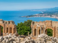 Италия. Сицилия. Таормина. Ruins of the Ancient Greek Theater in Taormina with the sicilian coastline. Province of Messina, Sicily, southern Italy. Фото e55evu-Deposit
