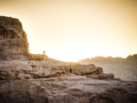 Иордания. Петра. Lone hiker standing on the rock in Petra, Jordan at sunset. Фото alexeys - Depositphotos