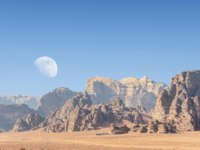 Incredible lunar landscape with huge moon in Wadi Rum village in the Jordanian red sand desert. Wadi Rum also known as The Valley. Фото leshiy985 - Deposit
