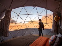 Asian tourist man in dome tent looking outside at Wadi Rum desert, famous natural attraction in Jordan. Фото zephyr18-Depositphotos