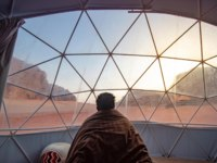 Tourist man staying in blanket in dome tent looking outside at Wadi Rum desert, famous natural attraction in Jordan. Фото zephyr18-Depositphotos