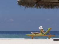 Мальдивы. Anantara Dhigu Resort & Spa, Maldives. Child on lounger looking out to sea