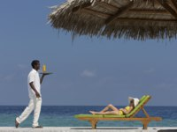 Мальдивы. Anantara Dhigu Resort & Spa, Maldives. Child on lounger being served a drink