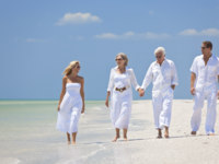 Мальдивы. Maldives. Two Couples Generations of Family Walking on Tropical Beach. Фото dmbaker - Depositphotos