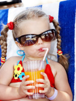 Мальдивы. Maldives. Child in glasses and red bikini drink juice. Фото poznyakov - Depositphotos