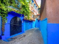 Клуб путешествий Павла Аксенова. Марокко. Шефшауен. Narrow street with blue painted walls in old medina of Chefchaouen. Morocco. Фото Bareta - Depositphotos