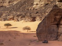 This is the canyon of Tadrart in the algerian desert of Tassili N'Ajjer. the Car in parked in the shade of a big rock. Фото foustanovitch@gmail.com - Depositphotos