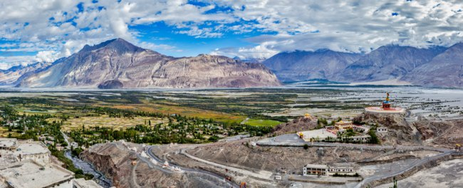 Panorama of Nubra valley in Himalayas with giant Buddha statue in Diskit, Ladakh, India. Фото DmitryRukhlenko - Depositphotos