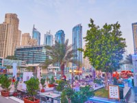 The green and cozy patio of the outdoor restaurant, located on shore of Dubai Marina in Dubai. Фото efesenko - Depositphotos