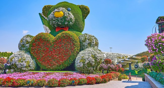 ОАЭ. Дубай. Сад чудес. The large installation of teddy bear, holding the heart of red flowers, Miracle Garden, on March 5 in Dubai. Фото efesenko - Depositphotos