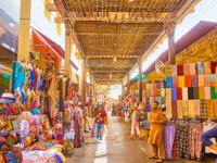 The narrow alleyway of Bur Dubai Grand Souq (bazaar, market), lined with stalls, offering garment, souvenirs, cashmere scarf. Фото efesenko - Depositphotos