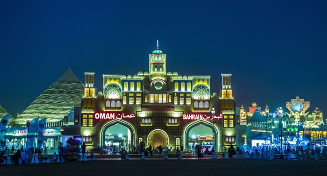 ОАЭ. Дубай. Всемирная деревня. General view of the central area at night in the park entertainment center Global Village. Dubai. UAE. Фото Observer - Depositphotos