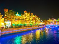 The colorful dancing fountains on canal of Global Village with a view on Africa pavilion, decorated with ethnic sculptures, bright lights in Dubai. Фото efesenko-Deposit