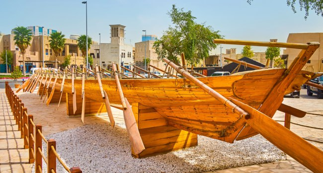 The rowing race boat with wooden paddles is set in the small square of Al Fahidi district, Dubai, UAE. Фото efesenko - Depositphotos