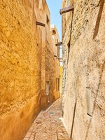Walk the narrow curved lane amid the blank walls of clay houses of Al Bastakiya (Al Fahidi) district of Dubai, UAE. Фото efesenko - Deposit