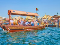 The tourists cross the Dubai Creek on traditional abra boat, floating between Deira and Bur Dubai districts in Dubai. Фото efesenko - Deposit