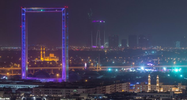 ОАЭ. Рамка Дубая в Забиль парке. Dubai Frame with Zabeel Masjid mosque illuminated at night timelapse. Фото neiezhmakov - Depositphotos