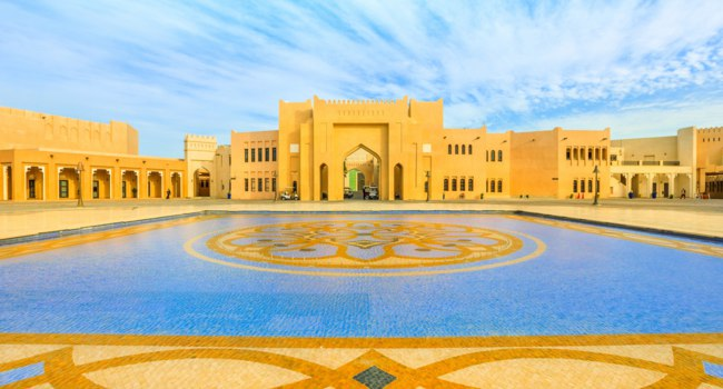 "Катар. Доха. Этнографическая деревня ""Катара"". Katara cultural village reflecting in a tiled pool with fountain in West Bay District. Фото bennymarty - Depositphotos"