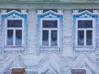 Золотое кольцо России. Гороховец. Light facade of a wooden house. Three windows with blue and white decorative wood carving frame. Folk style. Фото Orininskaya-Dep