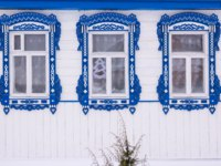 Золотое кольцо России. Гороховец. White facade of a wooden house. Three windows with decorative blue wood carving frame. Frost on windows. Фото Orininskaya-Dep