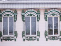 Золотое кольцо России. Гороховец. Pink painted facade of a wooden house. Three windows with green and white decorative wood carving frame. Snow. Фото Orinin