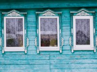 Золотое кольцо России. Гороховец. Green painted facade of a wooden house. Three windows with white decorative wood carving frame. Snow. Фото Orininskaya-Dep
