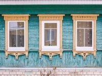 Золотое кольцо России. Гороховец. Green facade of a wooden house. Three windows with beige decorative wood carving frame. Snow. Folk style. Фото Orininskaya-Deps