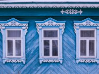 Золотое кольцо России. Гороховец. Blue painted facade of a wooden house. Three windows with decorative wood carving frame. Folk style. Фото Orininskaya - Deposi