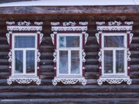Золотое кольцо России. Гороховец. Dark facade of a log wooden house. Three windows with white decorative wood carving frame. Folk style. Фото Orininskaya-Dep