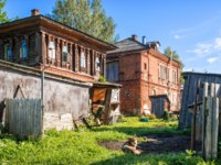 Кострома. A dog on a chain lies on the grass in the courtyard of an old abandoned wooden house in the village of Susanino. Фото yulenochekk-Deposit