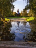 Музей-заповедник Костромская слобода. Wooden chapel on the background of the calm surface of an overgrown pond in the soft sunlight. Фото owsigor53-Deposit