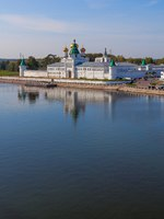 Кострома. Golden domes and white walls of a monastery on the river bank and its reflection in calm water against a blue sky background. Фото owsigor53-Deposit